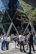 Lunchtime City workers enjoy drinks in summer sunshine beneath the Swiss Re building (aka The Gherkin), in the City of London, the capital's financial district (aka the Square Mile), on 22nd August 2019, in London, England.