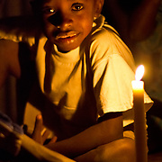 Koumbadiouma's children gather after dark in Peace Corps volunteer Rachael Honick's hut to do puzzles by candlelight. The village is not yet electrified. Kolda, Senegal.