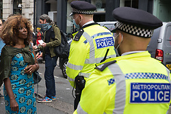 London, UK. 23rd August, 2021. Valerie Brown, Burning Pink London Mayoral candidate, speaks to a Metropolitan Police officer at a cordon around environmental activists from Extinction Rebellion in the Covent Garden area on the first day of Impossible Rebellion protests. Extinction Rebellion are calling on the UK government to cease all new fossil fuel investment with immediate effect. Credit: Mark Kerrison/Alamy Live News