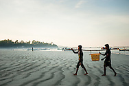 Myanmar, Ngapali. Two men bring their daily catch.<br /> Every single morning all the fisherman from the little village at Ngapali Beach come back home with their night catch. At the beach all the women wait for them and afterwards work with drying and selling fish and other creatures from the sea begins.
