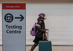 "© Licensed to London News Pictures. 24/11/2020. London, UK. A passenger walks past a Covid testing centre sign at London Heathrow Terminal 5 today. Minister for Transport Grant Shapps has announced that quarantine for air travellers will drop to 5 days from mid December if they take a private Covid test. Under the new ""test to release"" scheme passengers who test negative after 5 days self-isolation will be able to carry on with their normal lives. Photo credit: Alex Lentati/LNP"
