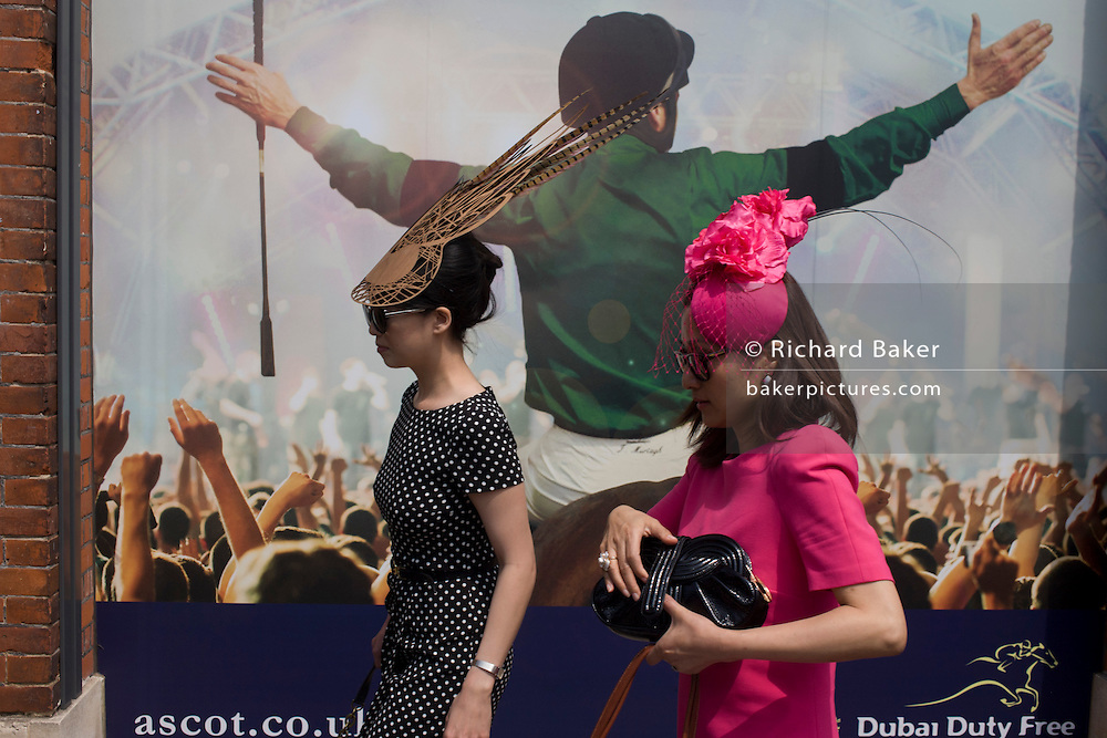 Ladies in fancy hats pass-by a jockey poster during the Royal Ascot horseracing festival in Berkshire, England. Royal Ascot is one of Europe's most famous race meetings, and dates back to 1711. Queen Elizabeth and various members of the British Royal Family attend. Held every June, it's one of the main dates on the English sporting calendar and summer social season. Over 300,000 people make the annual visit to Berkshire during Royal Ascot week, making this Europe's best-attended race meeting with over £3m prize money to be won.