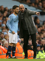Manchester City manager Pep Guardiola (right) has words with Manchester City's David Silva on touchline