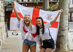 Licensed to London News Pictures. 11/07/2021. London, UK. England fans Lucy Willin 22 and Rebecca Thompson 22 from Luton wave flags in Covent Garden, London ahead of England's Euro 2020 finals match. England take on Italy in the Euro 2020 final at the iconic Wembley Stadium this evening. Photo credit: Alex Lentati/LNP