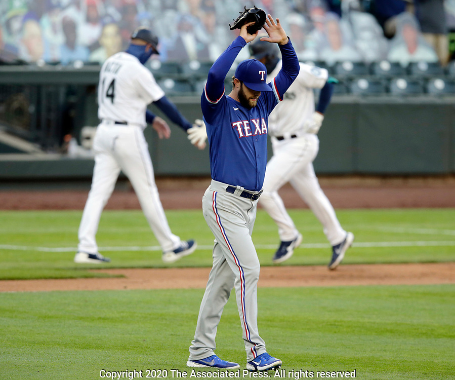 Texas Rangers starting pitcher Jordan Lyles stretches as Seattle Mariners' Evan White is congratulated by third base coach Manny Acta after hitting a home run during the third inning of a baseball game, Saturday, Aug. 22, 2020, in Seattle. (AP Photo/John Froschauer)
