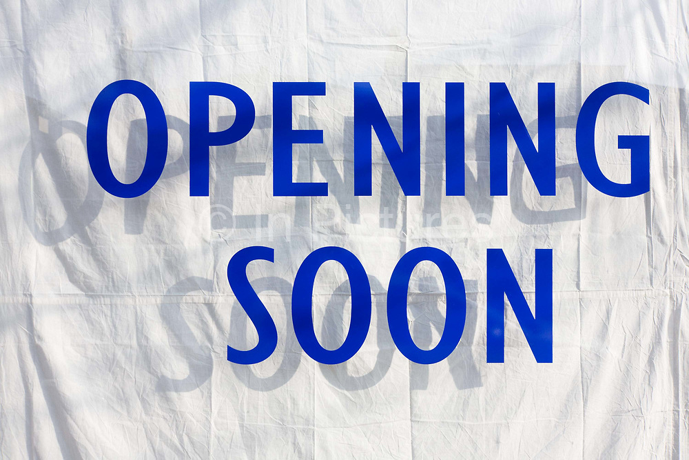 An Opening Soon sign announces a future new business. Written in prominent blue letters whose shadows that duplicates the message on a white sheet hiding the obscured window. The new shop will offer new jobs to local employees, a workforce anticipating a return to prosperity, a symbol of recovering economic growth.