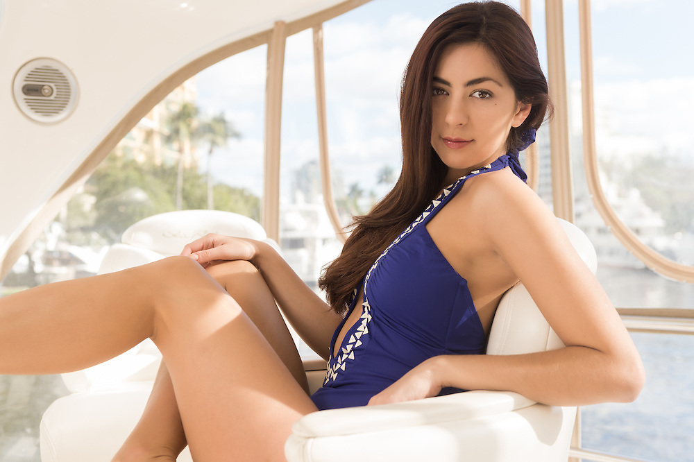 Portrait of young caucasian woman on a yacht capitan chair