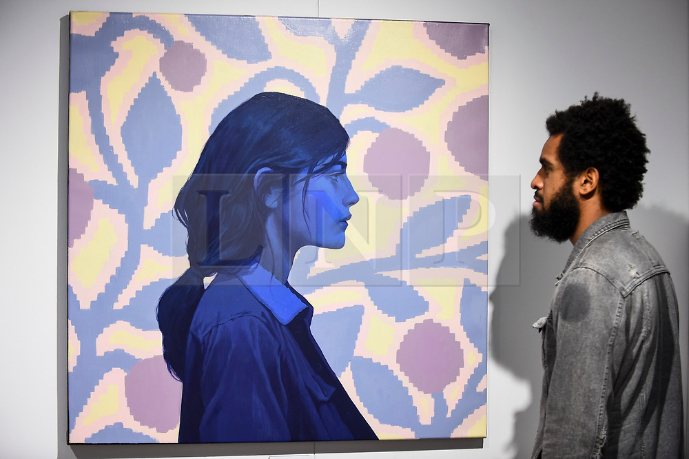 """© Licensed to London News Pictures. 04/10/2019. LONDON, UK. A visitor views """"The Blue Girl"""" by Bezt (ETAM) at the Thinkspace Projects stand at Moniker International Art Fair, an urban contemporary art fair taking celebrating its 10 year anniversary in the UK.  The fair is  place at Chelsea's Sorting Office air until 6 October 2019.  Photo credit: Stephen Chung/LNP"""