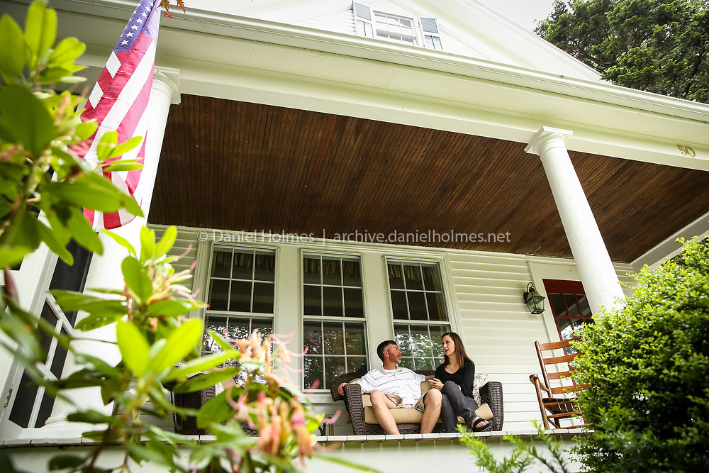 (6/14/14, HOLLISTON, MA) Lisa and Charlie Eppinger sit on the front porch of their antique home (c.1850) on Winter Street in Holliston on Saturday. Daily News and Wicked Local Photo/Dan Holmes
