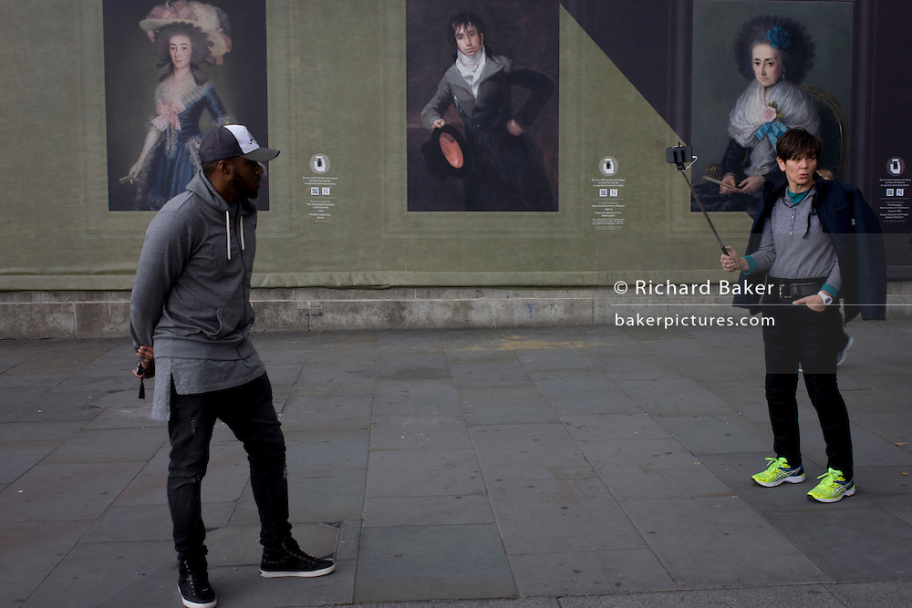 Street people near Goya portraits, sponsored by Credit Suisse and advertised on a construction hoarding outside the National Portrait Gallery.