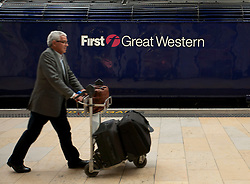 © Licensed to London News Pictures. 03/10/2012. LONDON, UK. A passenger walks past a First Great Western train in Paddington Station.  Photo credit: Matt Cetti-Roberts/LNP