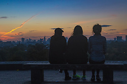 Primrose Hill, London, October 28th 2016. Three friends watch the city skyline as dawn breaks over London.