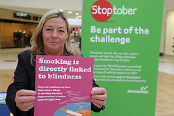 Poster saying Smoking is directly linked to blindness at Stoptober stall.