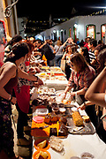 People buying cake in the street from a stall, Paraty, Rio de Janeiro, Brazil.