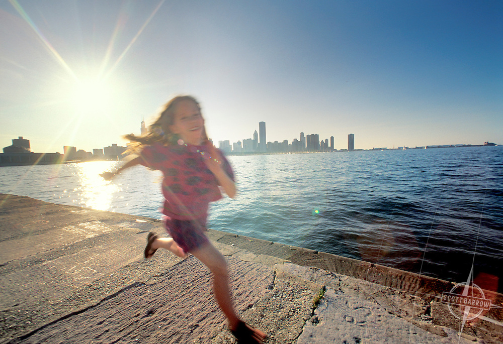 Laughing girl running by Lake Michigan, Chicago, IL.