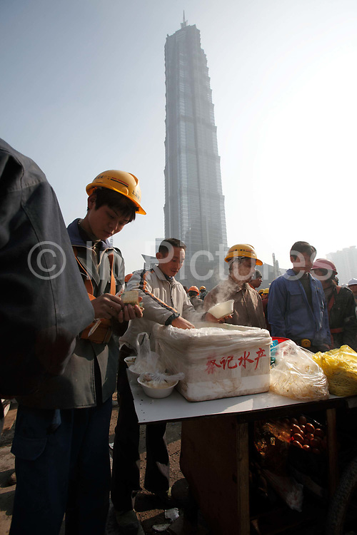 Construction workers gather together on a makeshift eating area in front of the Jin Mao Grand Hyatt Tower during lunch hour in Shanghai, China on 18 December, 2009. While China owes much of its recent economic revival to the vast and cheap labor force made up by hundreds of millions of migrant workers, it is facing an uncertain future as the number of able bodied workers have passed their peak and wage continues to rise.