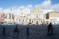 Kids in Naples, Italy play soccer on a public square at mid-day.