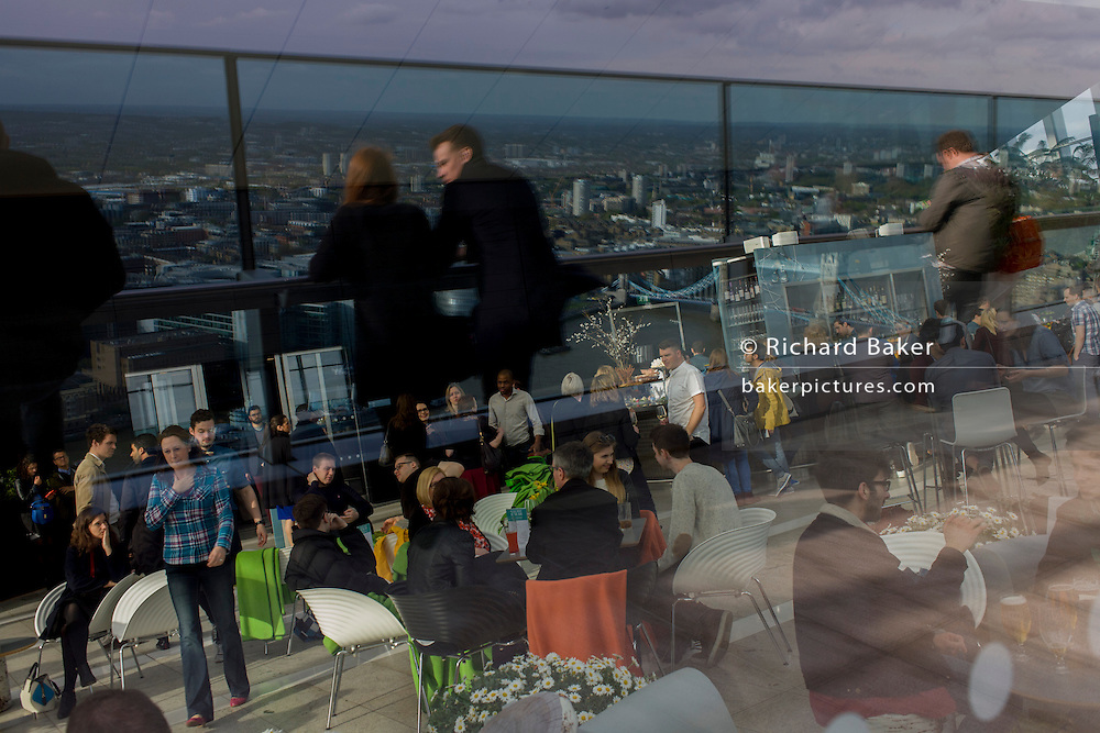 Visitors admire the London skyline from the Sky Garden of the Walkie Talkie building in the City of London.