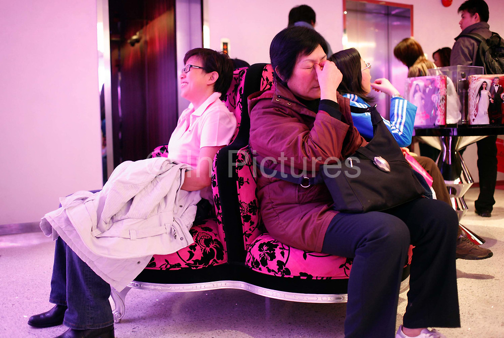 A tired grandparent at the new Barbie flagship store in Shanghai, China on 04 April, 2009. The six story store was opened in March this year to mark the 50th birthday of Barbie. The Barbie store has become a hit in Shanghai as a place where doting mothers take their daughters, often the only child in the family, for a girls' day out..