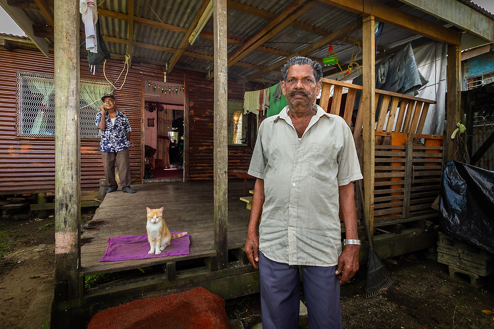 Wailea Settlment, Near Suva, Fiji   2011<br /> Sambhu Lal, 69, worked for thirty-three years at the Labasa sugar mill while his family cut sugar cane. Their land lease expired in 2004 and was not renewed, forcing them to move to the outskirts of Suva, where his son now works in a sawmill. He transported his house by truck and boat from Labasa and reassembled it on leased land in a squatter settlement popular with displaced cane farmers.