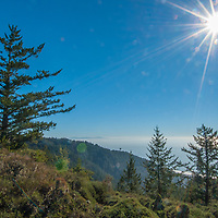 The sun hovers over the western slopes of Mount Tamalpais and the Pacific Ocean, north of San Francisco, California.