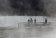 Tourists seen through the steam of the springs at Mammoth Hot Springs in Yellowstone National Park, Wyoming, USA