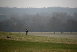 © Licensed to London News Pictures. 20/03/2015. Richmond, UK. A woman stands alone at the maximum eclipse.  People watch the cloudy sky darken during the near total eclipse at Richmond Park, Surrey today 20th March 2015. Photo credit : Stephen Simpson/LNP