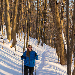A woman snowshoes in the forest on Indian Hill in West Newbury, Massachusetts.