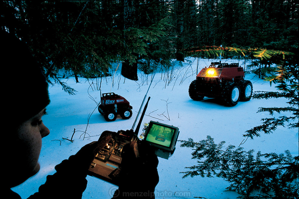 Radio-controlled outdoor mobile platforms, Micro ATRV and ATRV-2, are produced by Real World Interface, part of iRobot of Somerville, MA. (ATRV stands for All-Terrain Robot Vehicle.) Their main purpose: to carry equipment in and out of areas difficult for human beings to navigate. Looking at the liquid-crystal display for the Micro ATRV, a Real World staffer directs it toward its larger cousin. From the book Robo sapiens: Evolution of a New Species, pages 142-143.