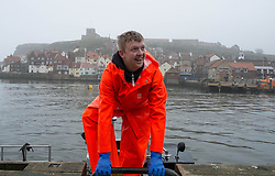 © Licensed to London News Pictures. 03/04/2014<br /> <br /> Whitby, North Yorkshire, United Kingdom<br /> <br /> A fisherman climbs from his boat onto the harbour wall as he shares a joke with a friend after returning from checking his lobster pots in Whitby, North Yorkshire.<br /> <br /> Photo credit : Ian Forsyth/LNP