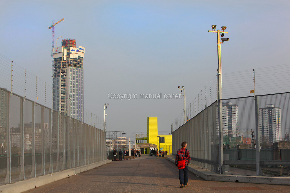 A visitor walks on the Greenway towards the yellow View Tube, a cafe, arts and Information center visible in the distance,  Olympic Park, London, United Kingdom. Picture by Manuel Cohen