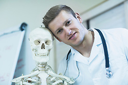 Portrait of a young doctor with skeleton in doctor's office, Freiburg Im Breisgau, Baden-Württemberg, Germany