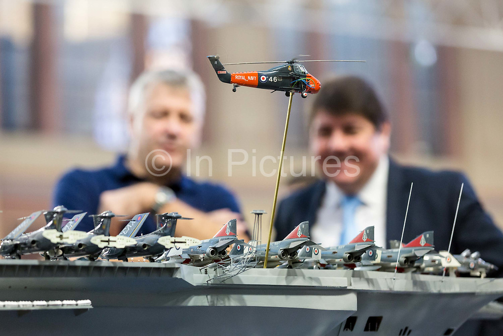 Dave Fortey L and Stephen Metcalfe MP, the new 2018 Government Envoy for the Year of Engineering look at details on Mr Forteys model of HMS Ark Royal R09 at the London Model Engineering Exhibition at Alexandra Palace on January 1st, 2018. Mr Fortey, a former Royal Navy mechanic and sub-lieutenant, built the model over 25 years and it is the first time it has been put on display to the public. This week, the Government has launched a campaign to inspire the next generation. The Year of Engineering, will see government and industry tackle a major skills gap and inspire the engineers of tomorrow.