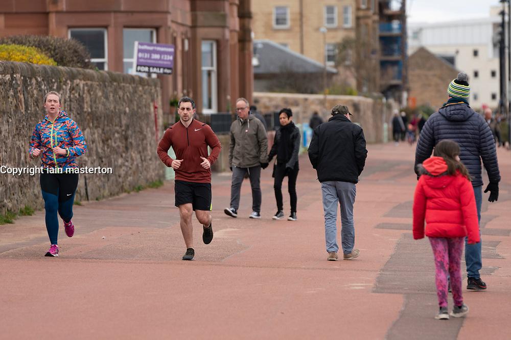 Edinburgh, Scotland, UK. 31 March, 2020. Despite Coronavirus lockdown members of the public are outside exercising and relaxing on Portobello promenade in Edinburgh. Iain Masterton/Alamy Live News