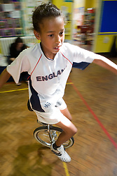 Young girl riding unicycle in school sports hall,