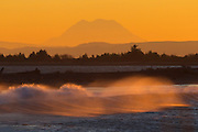 Large Pacific Ocean waves crash into the shoreline of Damon Point in Ocean Shores, Washington at sunrise. Mount Rainier, the tallest mountain in the state, is visible in the background.