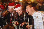 We see three friends close-up enjoying a festive party at Hamiltons pub in the City of London only a week before Christmas. It is a busy evening in the public house which is located near Liverpool Street mainline Station and they are in a humerous spirit just having fired off party streamers that have stuck to their clothes and faces. Two are wearing red and white santa claus hats but are stil in their work clothes. One is about to drink some of his pint of beer from a long, straight glass. The three look comical because of the streamers draped over their bodies and they are laughing and giggling at a joke that one has cracked. In the background a man is looking quizzically at the decorations.  The City of London has a resident population of under 10,000 but a daily working population of 311,000. The City of London is a geographically-small City within Greater London, England. The City as it is known, is the historic core of London from which, along with Westminster, the modern conurbation grew. The City's boundaries have remained constant since the Middle Ages but  it is now only a tiny part of Greater London. The City of London is a major financial centre, often referred to as just the City or as the Square Mile, as it is approximately one square mile (2.6 km) in area. London Bridge's history stretches back to the first crossing over Roman Londinium, close to this site and subsequent wooden and stone bridges have helped modern London become a financial success.