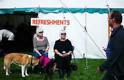 © Licensed to London News Pictures.26/08/15<br /> Egton, UK. <br /> <br /> Two women sit outside the refreshment tent at the 126th Egton Show in North Yorkshire. <br /> <br /> Egton is one of the largest village shows in the country and is run by a band of voluntary helpers. <br /> <br /> This year the event featured wrought iron and farrier displays, a farmers market, plus horse, cattle, sheep, goat, ferret, fur and feather classes. There was also bee keeping, produce and handicrafts on display.<br /> <br /> Photo credit : Ian Forsyth/LNP