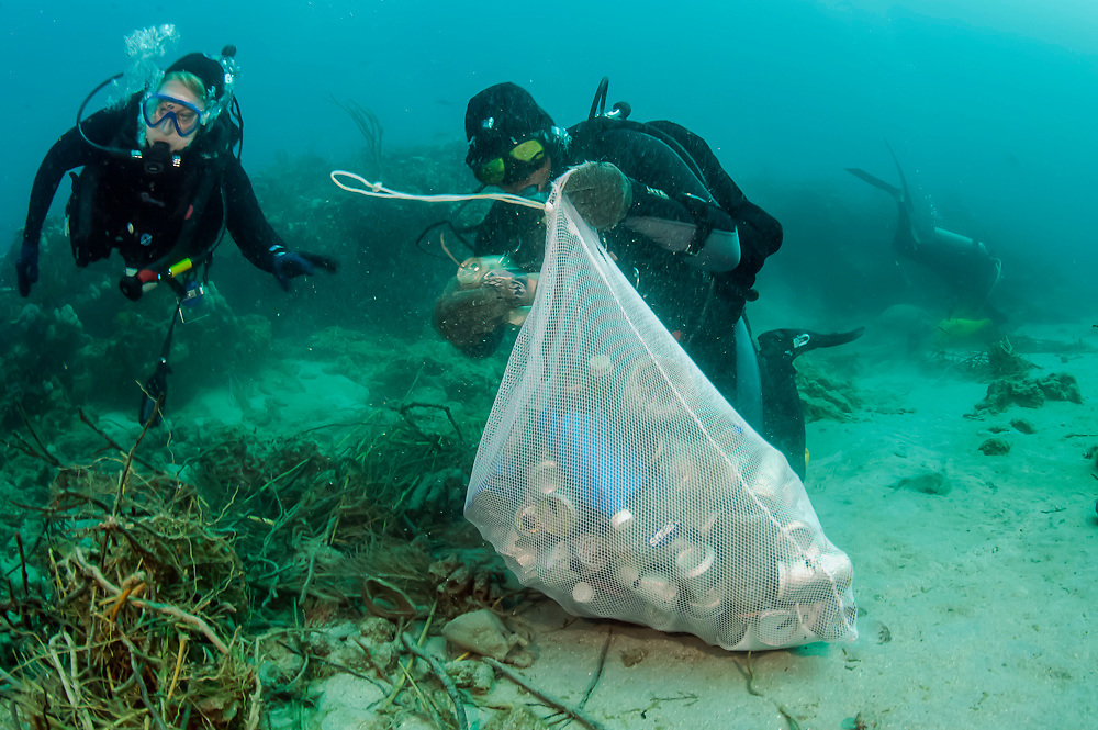 Scuba Divers picking up cans and garbage from a coral reef offshore Palm Beach, Florida, United States.