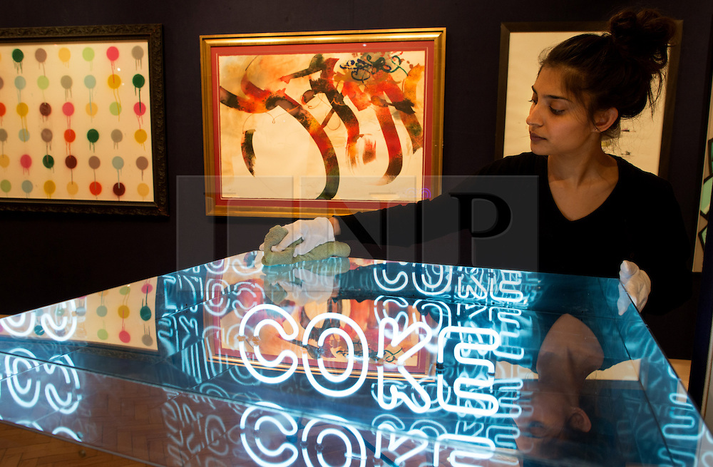 © Licensed to London News Pictures. 12/04/2013. London, UK. Gallery assistant cleans Pure Evil's Infinite Neon Coke during the preview for Climbing The Walls With Banksy at Bonham's Urban Art Sale at Bonham's auction house in London, April 12, 2013. Photo credit : Peter Kollanyi/LNP