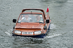 © London News Pictures. 03/07/2012.  Henley-on-Thames, UK. A couple ride in an amphibious vehicle on Day one of Henley Royal Regatta on the River Thames at Henley-on-Thames, Oxfordshire on July 03, 2013. Photo credit: Ben Cawthra/LNP