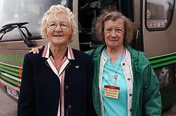 Two elderly women standing by a coach,