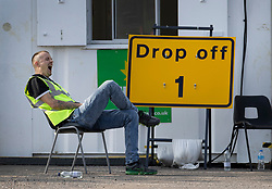 © Licensed to London News Pictures. 19/09/2020. Chessington, UK. A member of the Test & Trace staff waits for people to arrive at a Covid-19 testing centre set up in the car park of Chessington World of Adventures south west of London. The Government have faced criticism over delays in getting tested for the COVID-19 strain of coronavirus. . Photo credit: Peter Macdiarmid/LNP