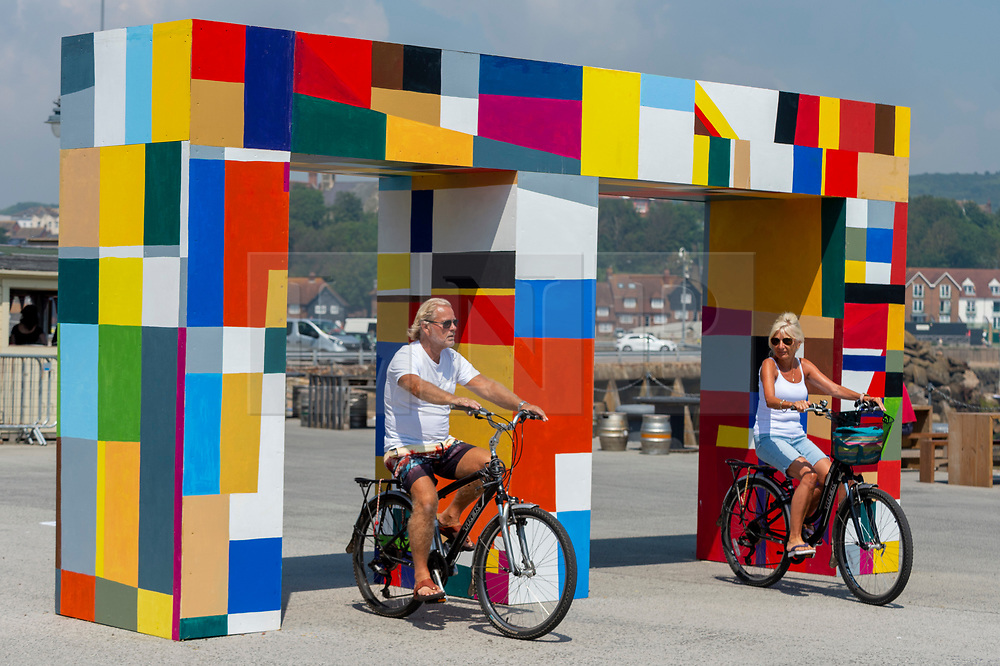 """© Licensed to London News Pictures. 20/07/2021. FOLKESTONE, UK. A couple cycles through """"Atsiaƒu ƒe agbo nu"""" (Gateways of the Sea), 2021, by Atta Kwami.  Preview of The Plot exhibition, the fifth Creative Folkestone Triennial. Folkestone has no publicly subsidised art gallery, so artists were invited to use public spaces to create new artworks in the seaside town. Over 20 works by artists including Assemble, Rana Begum, Gilbert & George, Atta Kwami, Pilar Quinteros, and Richard Deacon are on display 22 July to 2 November 2021.  Photo credit: Stephen Chung/LNP"""