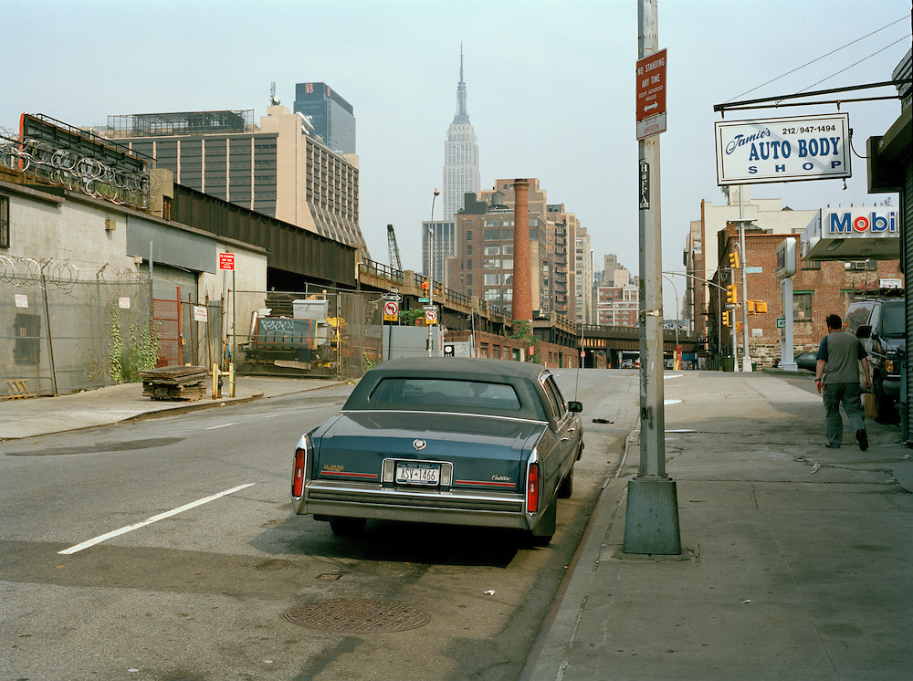 A Cadillac parked outside a car body shop on West 30th St, NYC. Empire State Building in the background.[Model Released pedestrian]<br /> [This photograph is currently licensed through GalleryStock - please contact the photographer for details]