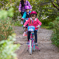 A woman and her two daughters ride bikes at Quoddy Head State Park in Lubec, Maine.