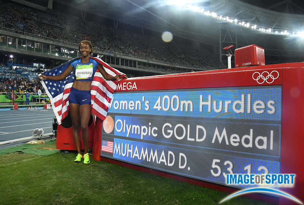 Aug 18, 2016; Rio de Janeiro, Brazil; Dalilah Muhammad (USA) poses with United States flag and scoreboard after winning the women's 400m hurdles in 53.13 during the 2016 Rio Olympics at Estadio Olimpico Joao Havelange.