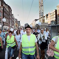 Nederland, Amsterdam , 23 juli 2014.<br /> Duizenden mensen lopen mee met een stille tocht door het centrum van Amsterdam. Volgens de organisatie zijn er zo'n vijfduizend deelnemers, meldt persbureau Novum. De wandeling begon om 20.00 uur op de Dam en eindigt daar ook weer. Deelnemers zullen daar witte ballonnen oplaten. Ook dragen zij witte kleding.<br /> Op de foto: in het midden vooraan loopt de organisator van de Stille Optocht Peter van Lent.<br /> Thousands of people in white clothes walk along with a silent march through the center of Amsterdam. The victims of flight MH17 are thus commemorated. National day of Mourning .