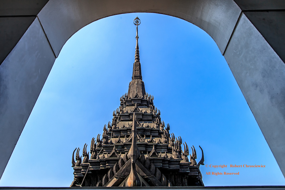 Framed Spire: The deep inset of the window frames the scene of an ornate, multi tiered black spire with numerous mystical Chofa, Wat Ratchanada, Bangkok Thailand.