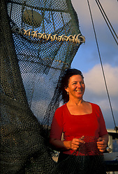 Stock photo of a woman holding a net on a large fishing boat